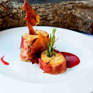 Rulo de cochinillo y boletus albardado en bacon con salsa de frambuesa